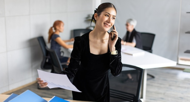 Smiling  asian entrepreneur woman busy working talking on mobile phone in home office. banner background copy space