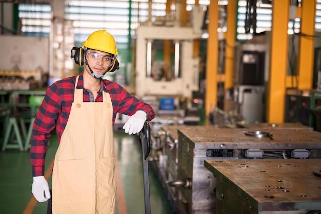 트롤리에서 격자 무늬 빨간 셔츠, 헬멧, 안전 안경을 쓴 웃는 아시아 공장 젊은 노동자