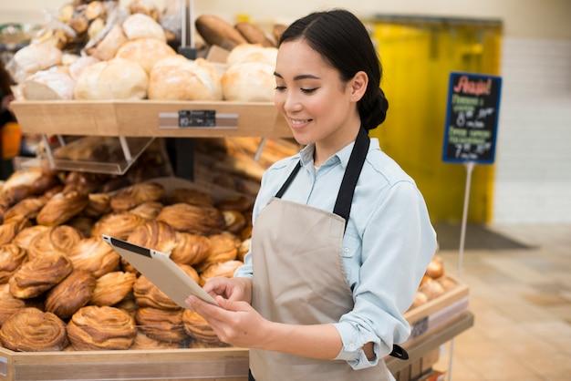 Усмехаясь азиатский женский продавец хлебопекарни стоя с таблеткой в супермаркете