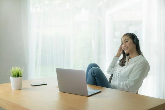 Улыбающаяся азиатская женщина в повседневном взгляде работает с наушниками и портативным компьютером на столе у себя дома.
