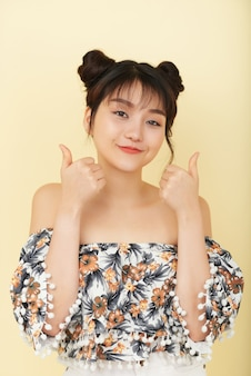 Smiling asian girl in bare shoulder top posing in studio with thumbs up