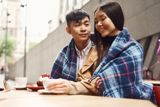 Smiling asian girl and boy romantic date in cafe.