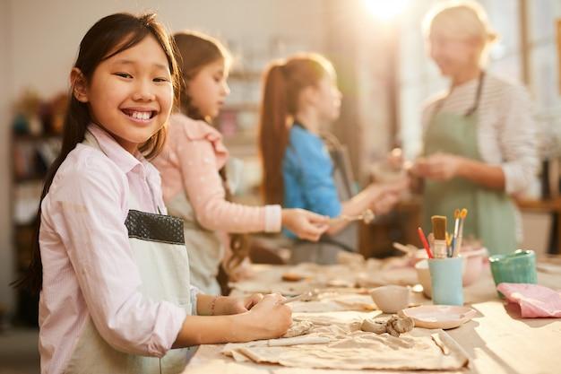 Улыбающаяся азиатская девушка в гончарной мастерской