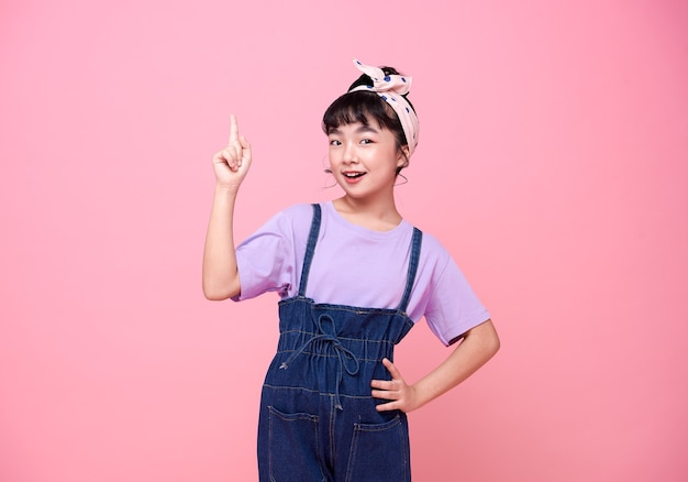 Улыбающаяся азиатская девушка указывая пальцем на пустое пространство рядом с розовой изолированной стеной
