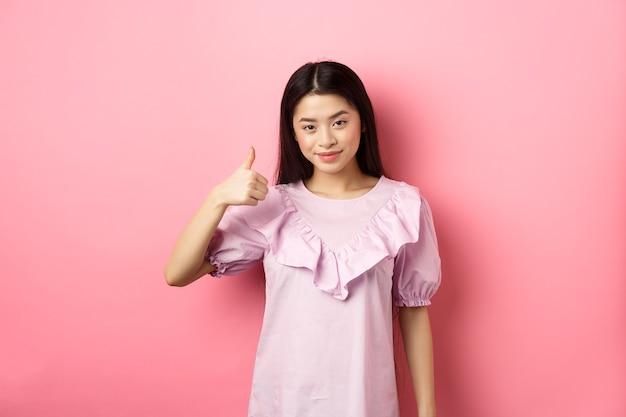 笑顔のアジアの女の子は、承認で親指を立てて、良い選択を賞賛し、立っている製品をお勧めします...