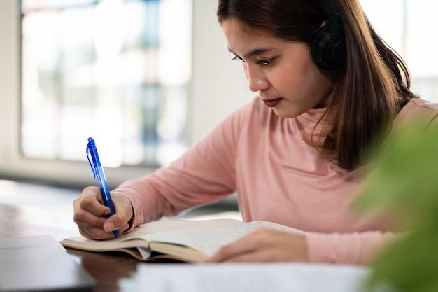 Улыбающаяся азиатская студентка носит беспроводные наушники, пишет на ноутбуке, чтобы изучать язык онлайн, смотреть и слушать лектора, веб-семинар с помощью видеозвонка, электронное обучение на дому, дистанционное обучение