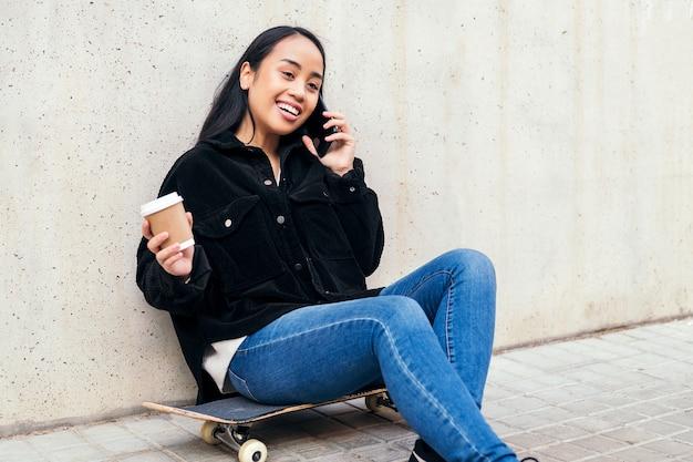 콘크리트 벽에 기대어 스케이트보드에 앉아 야외에서 전화 통화를 하는 웃고 있는 아시아 소녀
