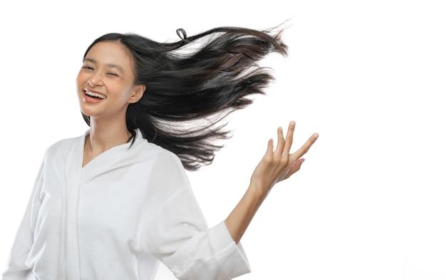Улыбающаяся азиатская девушка в полотенце стоит с длинными черными волосами, развеваемыми ветром