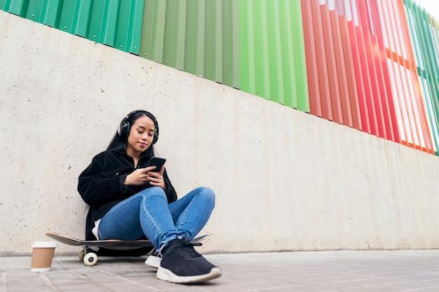 야외에서 콘크리트 벽에 기대어 스케이트보드에 앉아 헤드폰으로 음악을 들으며 웃고 있는 아시아 소녀