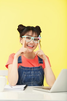 Smiling asian girl with topknots, in brightly colored glasses sitting at desk with laptop