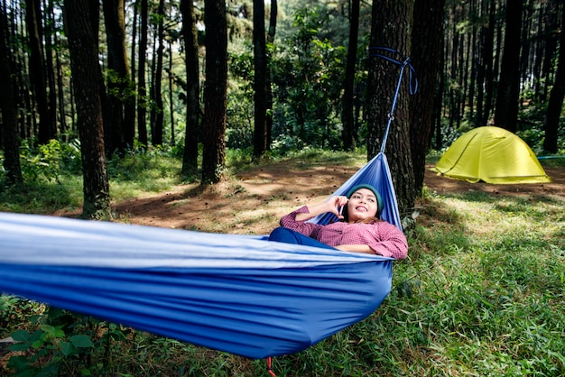 Smiling asian hiker woman talking on cellphone while lying in hammock