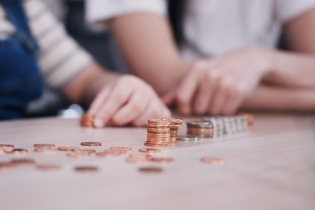 笑顔のアジアの小さなアジアの女の子の子供は、木製のテーブルに母親と一緒に将来のためにお金を節約するために、木製のテーブルにコインを数えています。ホームスクールの概念のための子供教育。