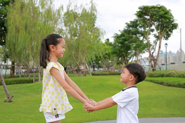 정원에서 함께 노는 동안 손에 손을 잡고 웃는 아시아 어린 소년과 소녀.