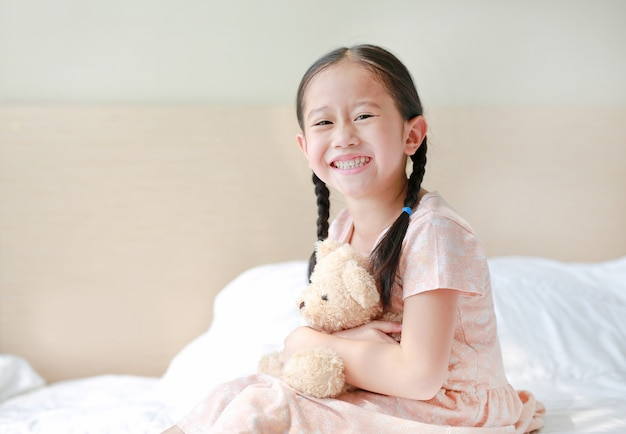 Smiling asian little girl cuddle teddy bear sitting on the bed at home