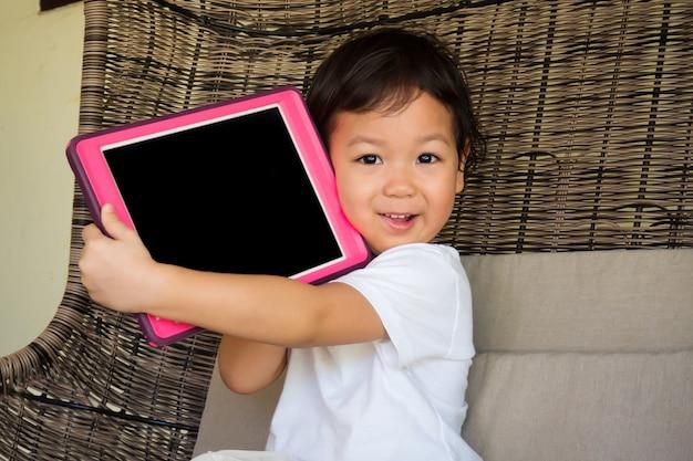 彼女の手でタブレットを保持しているアジアの少女の笑みを浮かべてください。技術と子供との幸せの時間の概念。