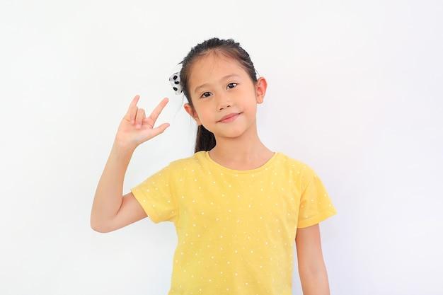 Улыбающаяся азиатская маленькая девочка, показывающая пальцем, я люблю тебя, символ языка жестов