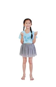 立っているピグテールの髪と白で隔離の手を上げて笑顔のアジアの小さな子供の女の子
