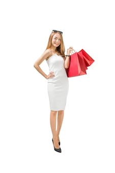 Smiling asian luxury woman carrying red shopping bags standing