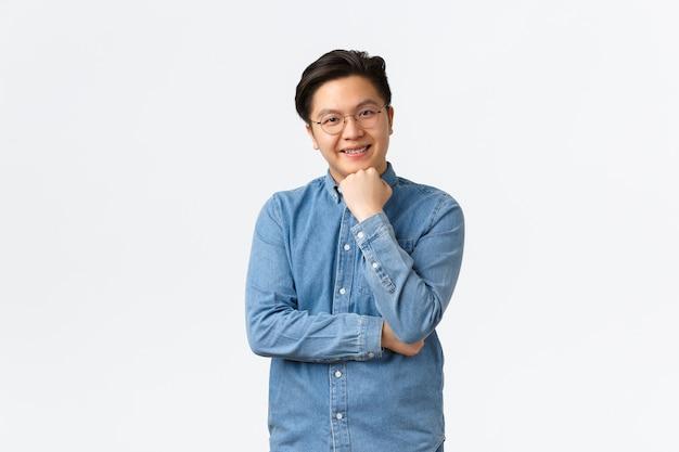 웃고 있는 아시아 남학생, 파란색 셔츠와 안경을 쓴 프리랜서, 관심을 갖고 듣고, 대화를 하는 동안 고개를 끄덕이고, 손에 기대고, 호기심을 갖고, 무언가를 공부하고, 흰색 배경.