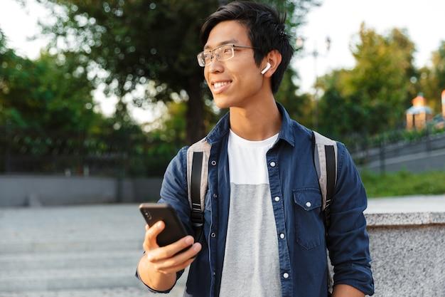 屋外を見ながらスマートフォンを保持している眼鏡とイヤホンで笑顔のアジアの男子学生