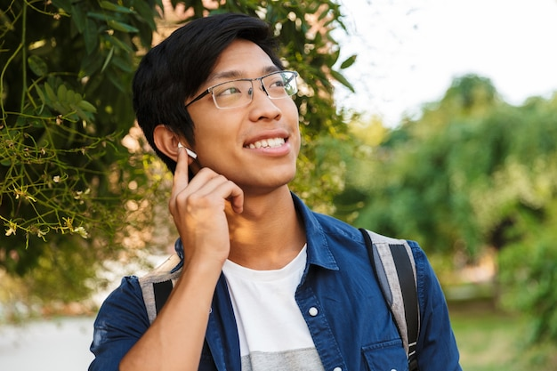Улыбающийся азиатский студент-мужчина в очках слушает музыку и смотрит в сторону на открытом воздухе