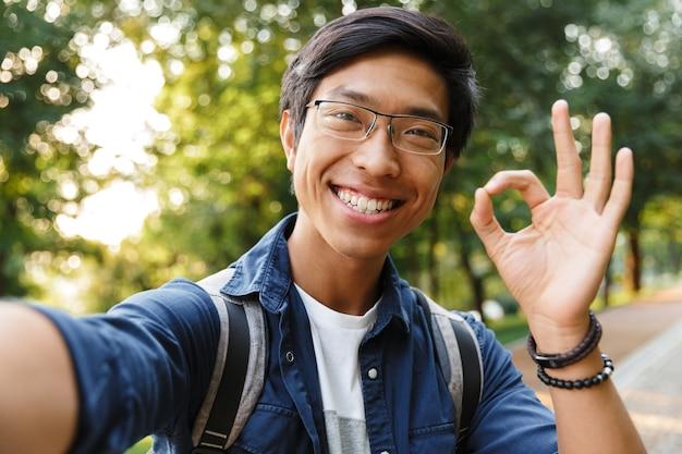 屋外でカメラを見ながら自分撮りをし、okサインを示す眼鏡で笑顔のアジア人男子学生