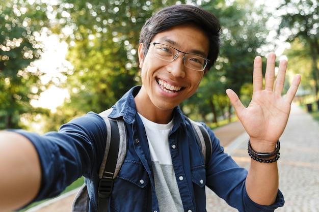 自撮りをし、屋外のカメラで手を振る眼鏡で笑顔のアジアの男子学生