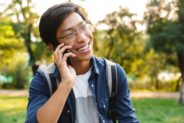 スマートフォンで話し、公園にいる間目をそらしている眼鏡で笑顔のアジアの男子学生