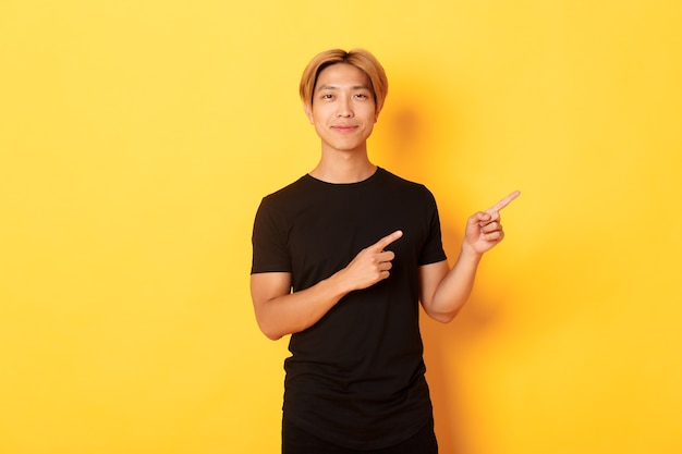 Smiling asian male student with blond hair, pointing fingers right, showing logo, standing yellow wall.