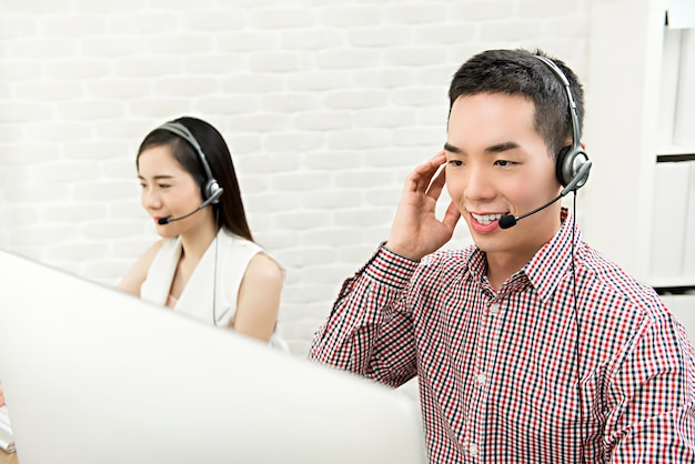 Smiling asian male telemarketing customer service agent working in call center