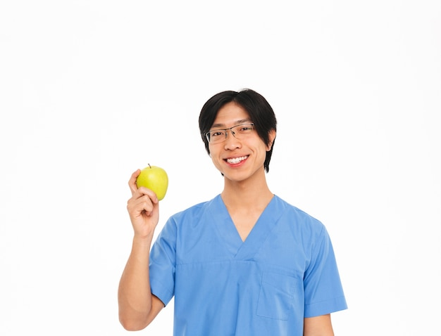 笑顔のアジア人男性医師が白い壁の上に孤立して立っている制服を着て、青リンゴを示しています