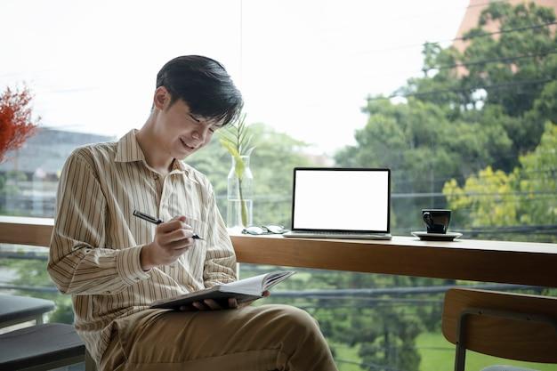 現代のコーヒーショップに座って、ノートに新しいアイデアを書いている笑顔のアジア人フリーランサー。