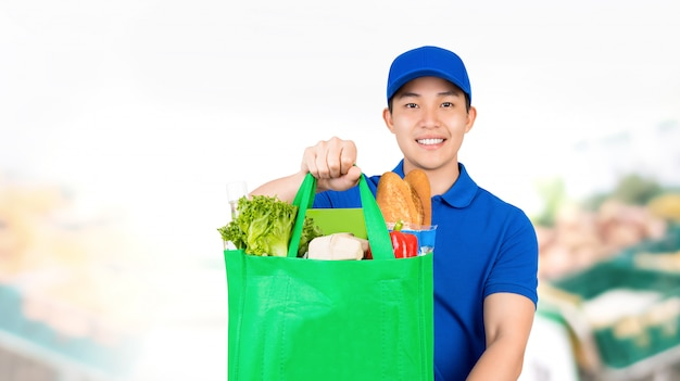 Smiling asian man holding grocery shopping bag in supermarket offering home delivery service