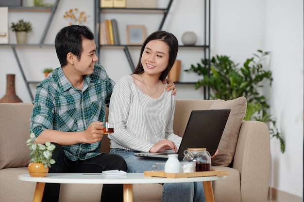 웃고 있는 아시아 남성이 집에서 노트북 작업을 하는 여자 친구를 껴안고 차 한 잔을 제공합니다.