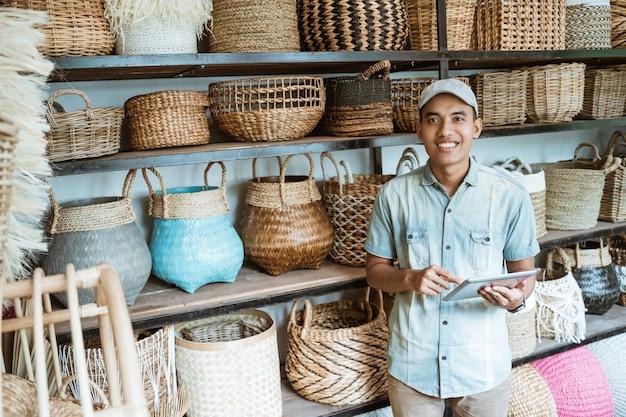 手作りのバッグを持って立っている間パッドを保持しながら見ている笑顔のアジア人男性