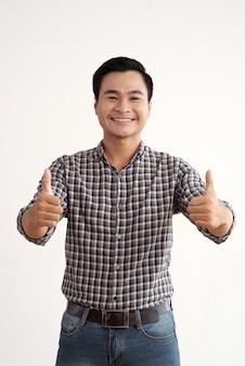親指でスタジオでポーズをとって笑顔のアジア人