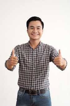Smiling asian man posing in studio with thumbs up