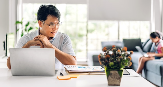 Усмехаясь азиатский человек ослабляя используя работу портативного компьютера и беседу встречи видеоконференции с его дочкой девушки используют изучение портативного компьютера с системой электронного обучения онлайн образования дома