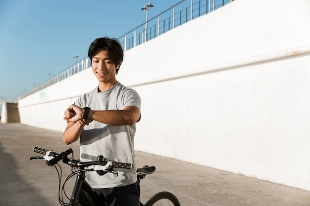Smiling asian man riding a bicycle outdoors, checking time