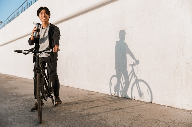 Smiling asian man riding a bicycle outdoors, drinking water from a bottle