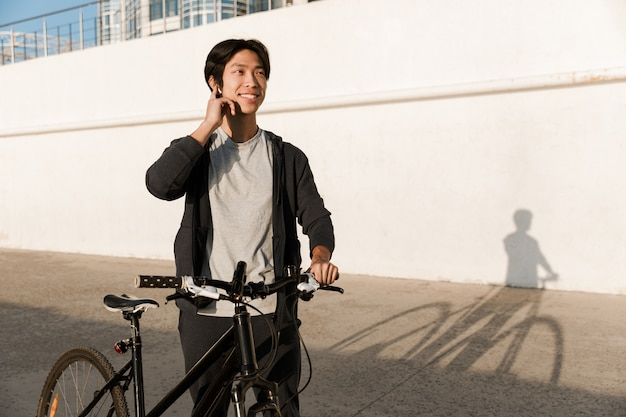 Smiling asian man riding a bicycle outdoors, talking on mobile phone
