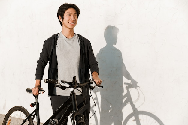 Smiling asian man riding a bicycle outdoors