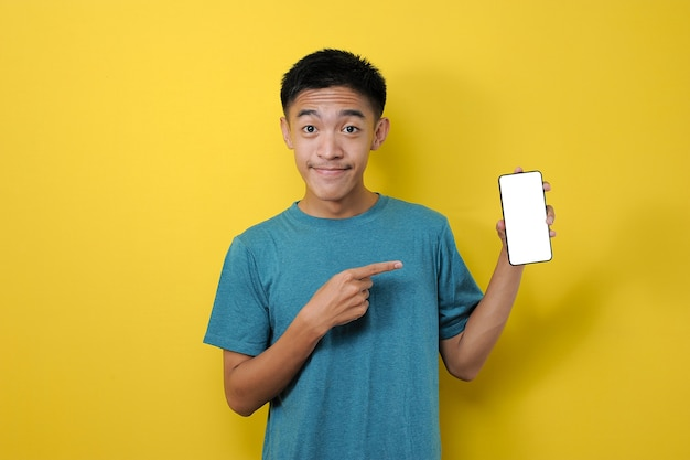 Smiling asian man showing on empty smartphone screen, pointing at mobile phone and looking satisfied, isolated on yellow background