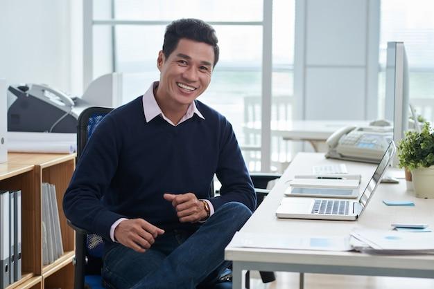 オフィスでラップトップの前の机に座って、カメラ目線のアジア人の笑みを浮かべてください。