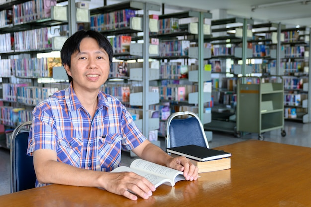 Smiling asian man student working in a library