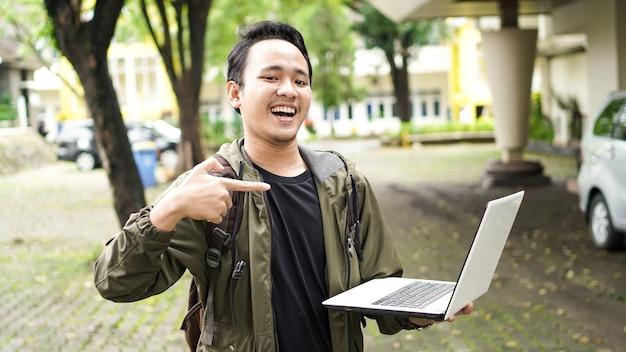노트북에서 지적 배낭을 입고 웃는 아시아 남자