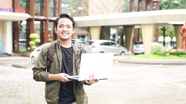 노트북 가방을 입고 웃는 아시아 남자