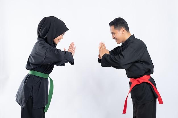 プンチャックシラットのユニフォームを着た笑顔のアジア人男性と女性は、お互いに敬意を表してお辞儀をして向かい合って立っています