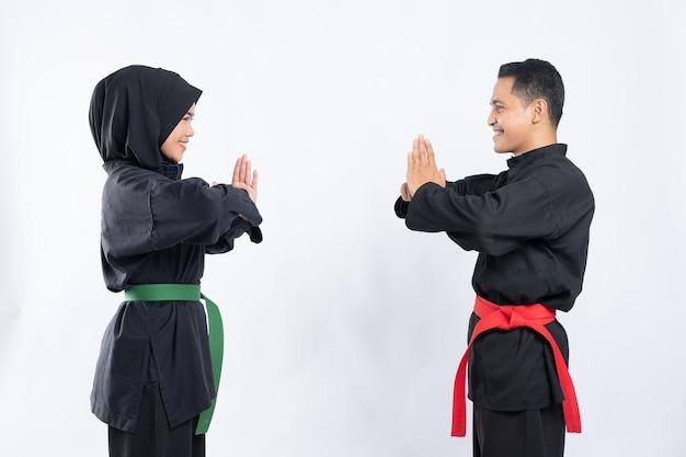 プンチャックシラットの制服を着た笑顔のアジア人男性と女性は、敬意を表して向かい合って立っています