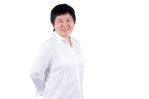 白い背景で隔離の白いシャツの笑顔アジアの中年女性
